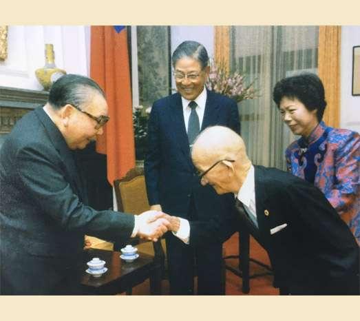 20200915-1985年11月5日,已故前總統李登輝獲頒一等卿雲勳章,父親李金龍觀禮,與故總統蔣經國握手。(取自總統府)
