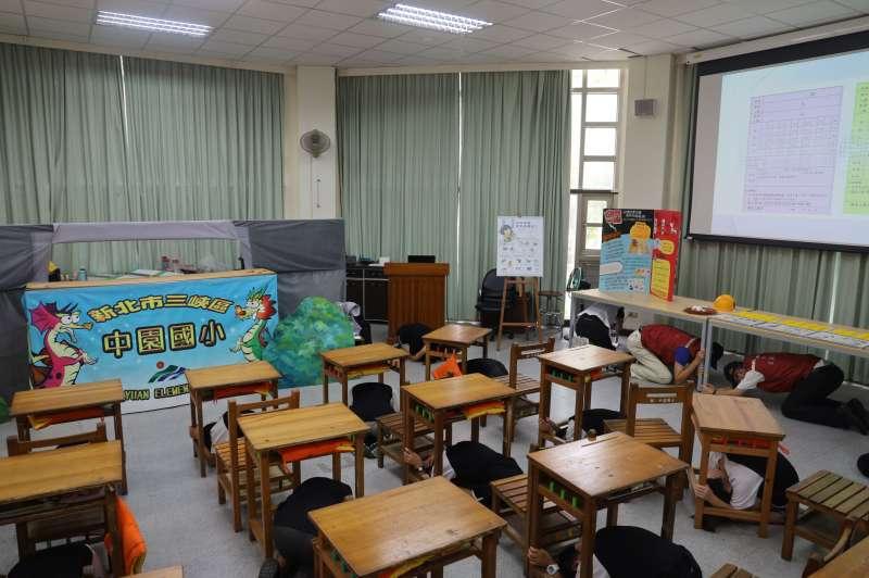 副市長謝政達及現場來賓和學生示範地震來時進行「趴下、掩護、穩住」避震三步驟。(圖/新北市教育局提供)