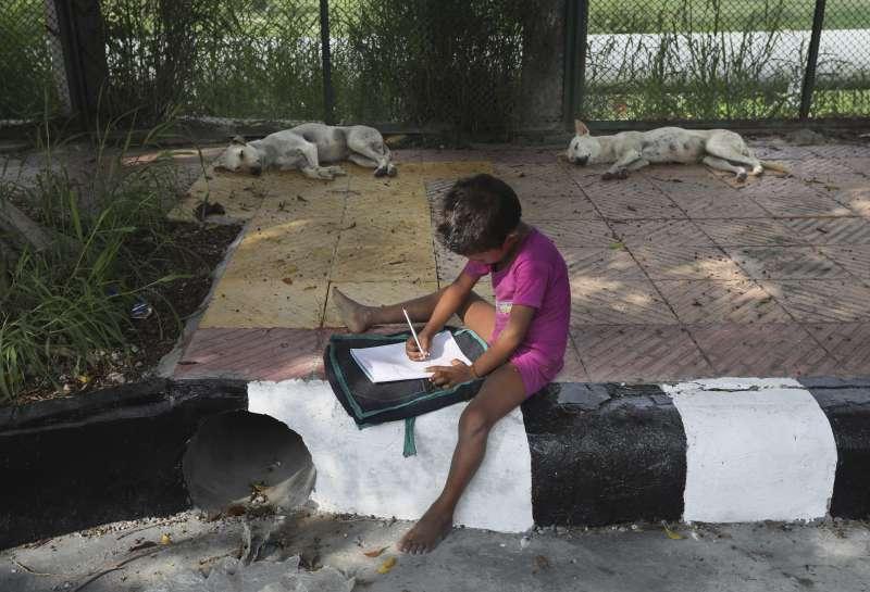 新德里街頭學校:印度新冠疫情持續延燒,家境貧困的孩童無法改採線上學習、面臨失學危機。(AP)
