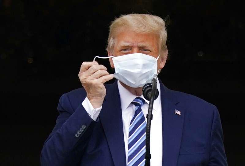 美國總統川普10日首度進行公開活動,現身白宮「杜魯門陽台」對數百名支持者談話,他在發言時還特地摘下口罩。(美聯社)