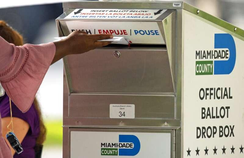 一位邁阿密的選民10月28日將選票放進投票箱。(美聯社)
