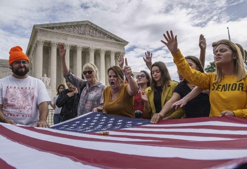 一群基督教福音派人士在最高法院外,國旗上擺著塑膠胚胎模型以強調反墮胎立場。(AP)