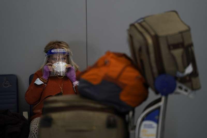 美國感恩節前夕出現旅遊潮,機場旅客全副武裝不敢大意。(美聯社)