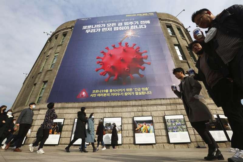 南韓首爾市政廳的巨幅新冠病毒宣導海報,街上的市民則大多戴著口罩。(美聯社)