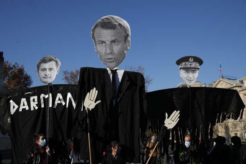 11月28日法國萬人上街抗議《整體安全法》草案,示威者高舉內政部長達馬南、總統馬克宏和巴黎警署署長拉勒蒙的假人。(美聯社)