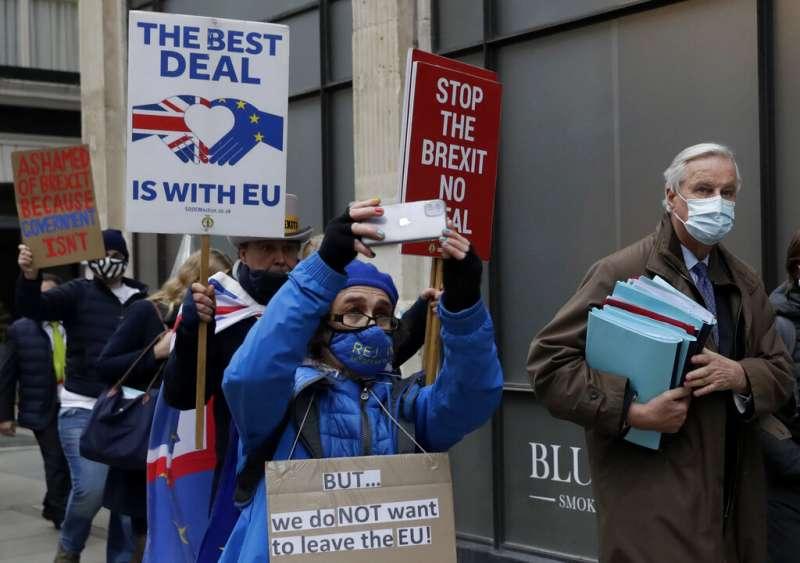 脫歐談判代表巴尼耶(Michel Barnier),他身後的倫敦民眾正高舉「反對無協議脫歐」的標語。(美聯社)