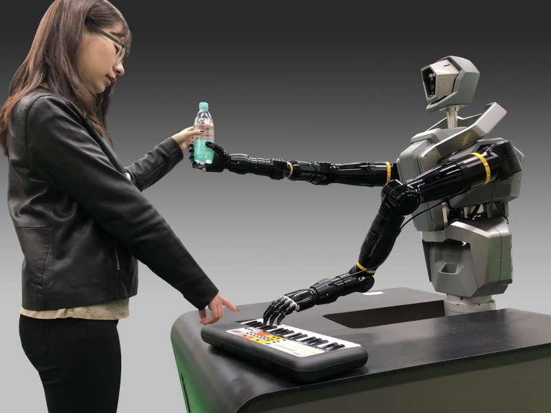工研院在CES展出的類人雙臂機器人,擁有仿生手掌抓取形狀不規則物件,拿書、名片、手機、或寶特瓶,連彈電子琴都可以。(圖/工研院提供)