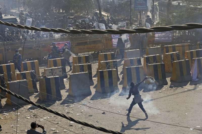2020年1月26日,印度農民示威者與警方爆出衝突,圖為示威者將催淚彈丟回警方。(AP)