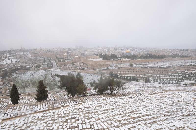 2021年2月,中東下起罕見大雪。雪花覆蓋了以色列橄欖山的墓園,遠方可見阿克薩清真寺圓頂。(AP)