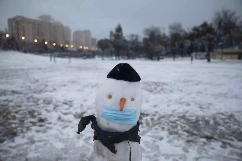 2021年2月,中東下起罕見大雪,導致交通、學校、甚至新冠疫苗施打計劃暫時延宕。圖為耶路撒冷的雪人帶上口罩。(AP)