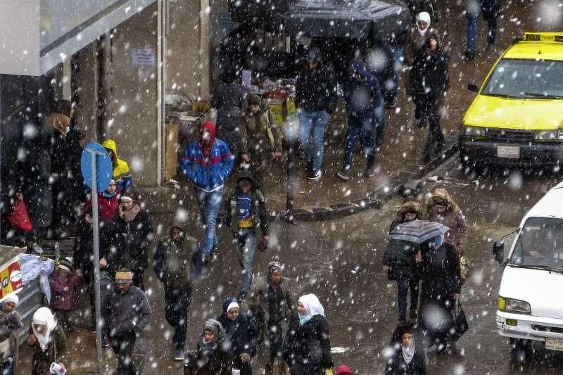 2021年2月,中東下起罕見大雪,圖為敘利亞民眾走在下雪的大馬士革街頭。(AP)