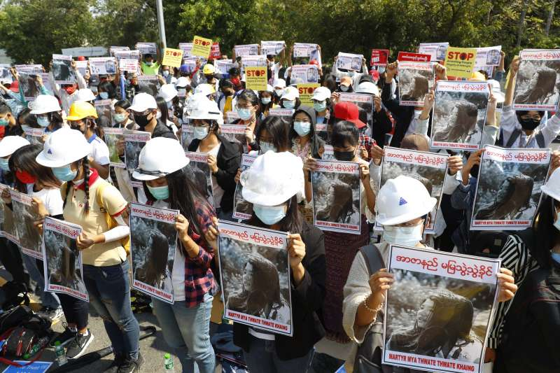 緬甸少女示威者苗兌兌凱頭部中彈不治,民眾持她的照片聚集抗議。(AP)
