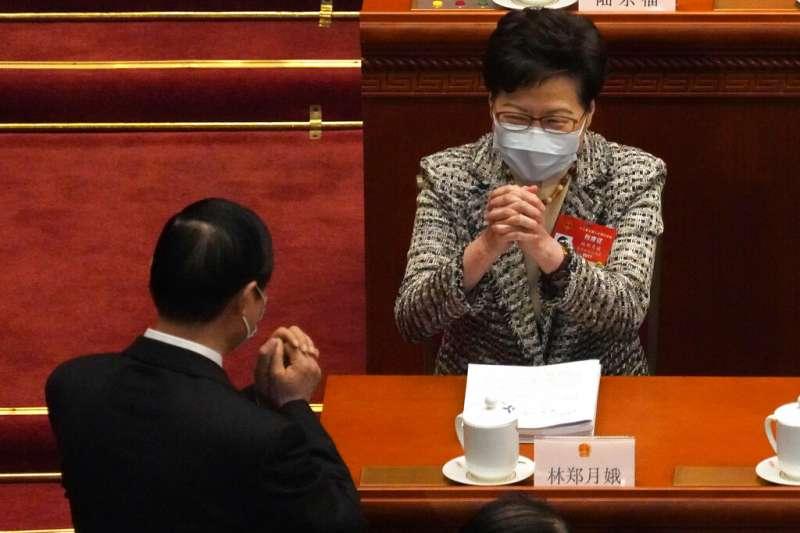 赴北京參加兩會的香港特首林鄭月娥與其他代表打躬作揖。(美聯社)
