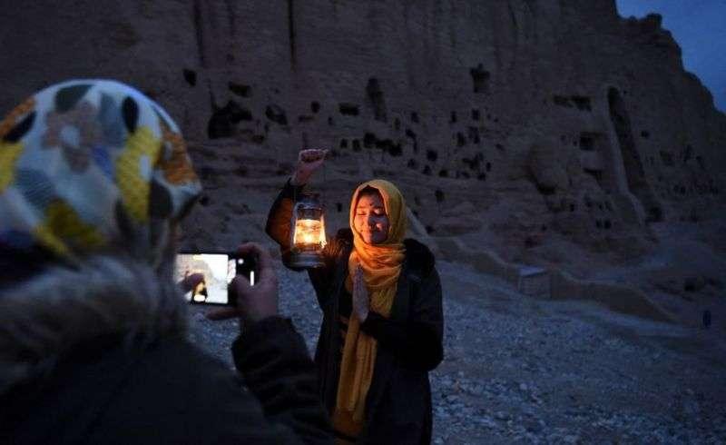 一位婦女在雕像山坡附近擺好姿勢凖備拍照。(BBC News中文)