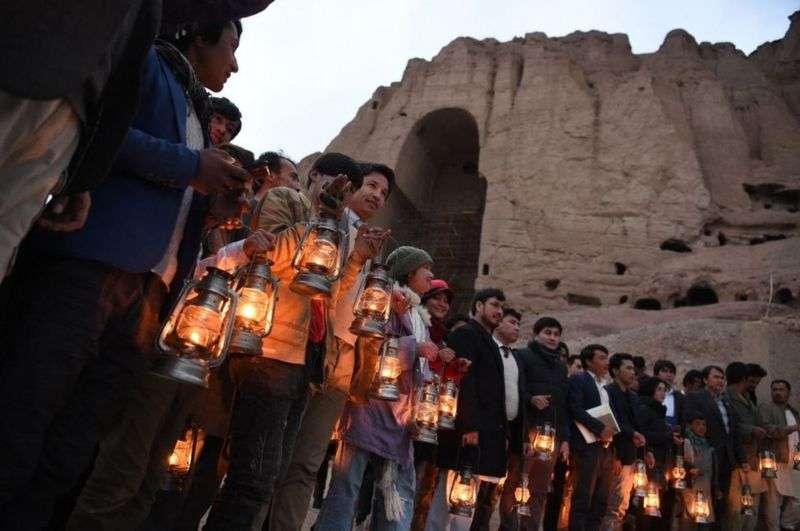 數百人聚集在懸崖邊,旁邊為古老洞穴。(BBC News中文)