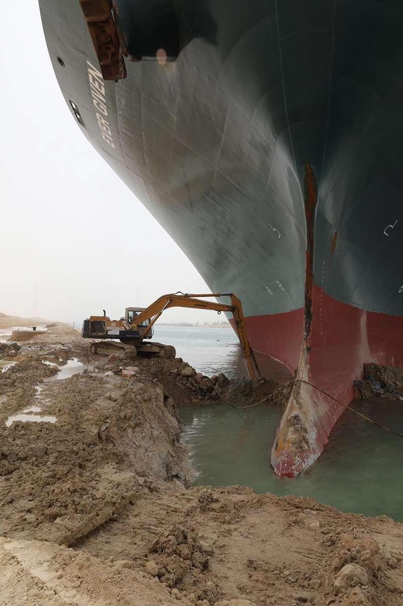 2021年3月23日,台灣長榮海運租用的貨櫃輪「長賜輪」卡住埃及蘇伊士運河,挖土機試圖清除淤泥(AP)