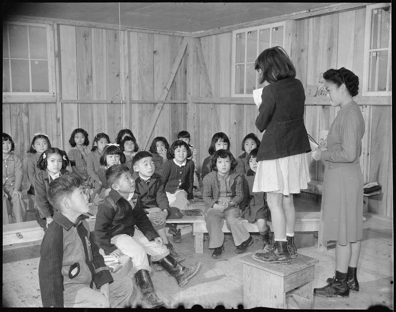二戰期間,交戰雙方都設置集中營扣留敵國人民。日軍在中國、日本設置,關押英美平民;美國也扣押囚禁了約 11 萬日裔美國人。圖中即為美國集中營內的日本學童,戰後美國政府歷經訴訟,道歉賠償。(圖/研之有物提供)