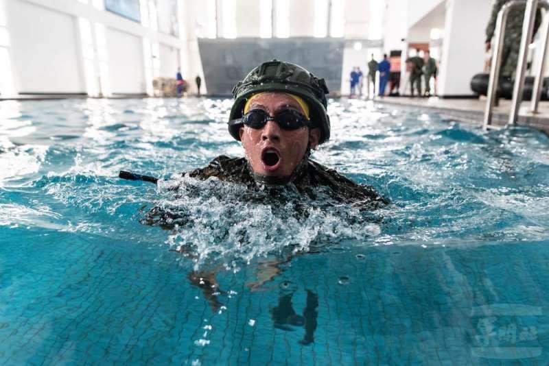 學員在身著迷彩服、戴頭盔、大背槍的情況下,於7分半內完成200公尺武裝蛙泳。(取自軍聞社)