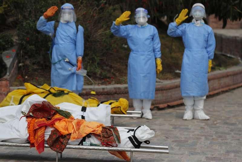 尼泊爾新冠肺炎疫情嚴峻,全副武裝的軍人向準備火葬的病逝者敬禮。(AP)