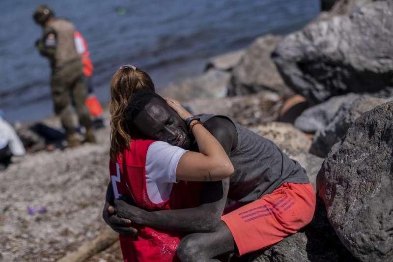 2021年5月,西班牙海外領土休達市湧入8000位移民,多數都是摩洛哥人。紅十字會義工安撫抵達休達者。(AP)