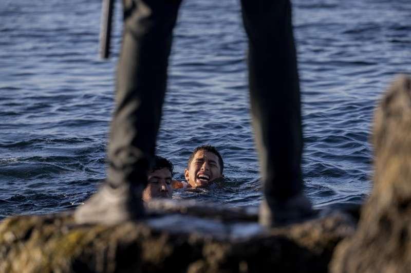 2021年5月,西班牙海外領土休達市湧入8000位移民,多數都是摩洛哥人。守衛在岸邊等待游泳前往休達者。(AP)
