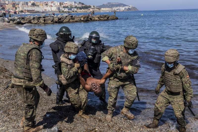 2021年5月,西班牙海外領土休達市湧入8000位移民,多數都是摩洛哥人。西班牙軍人驅逐試圖前往休達的移民。(AP)