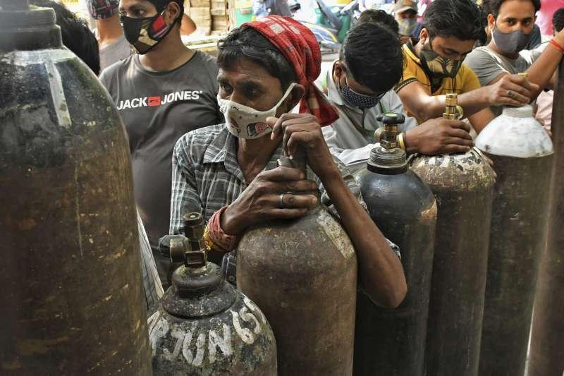 新冠疫情下的缺氧危機:印度民眾等待為氧氣瓶打氣。(AP)