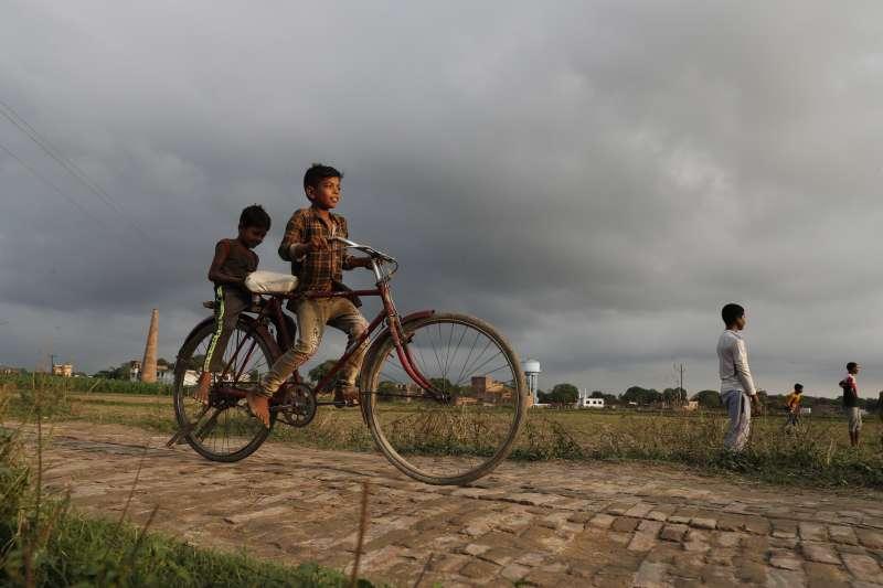印度新冠疫情曲線趨緩,位於恆河沿岸的普拉亞格拉傑(Prayagraj)孩童騎車玩耍。(AP)