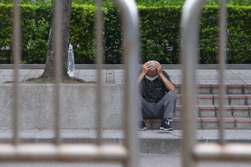 20210605-疫情下的萬華街頭,民眾抱頭坐於階梯。(顏麟宇攝)