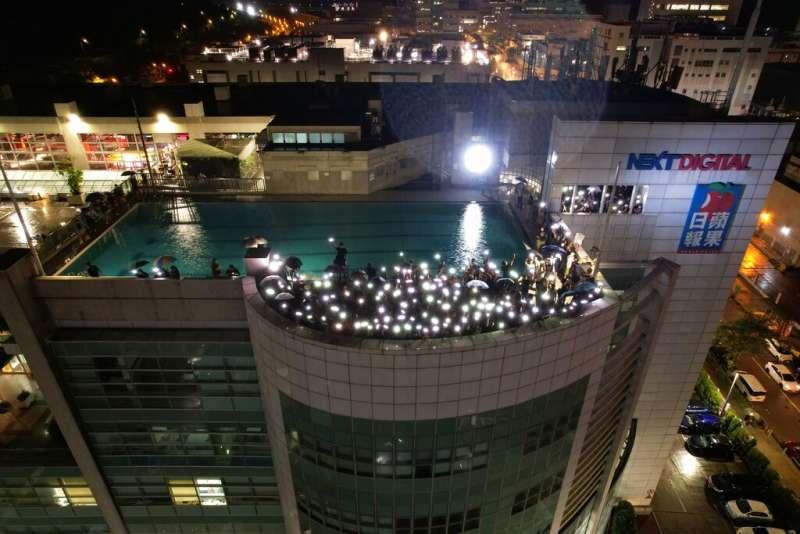 香港《蘋果日報》的最後一夜,員工聚集在天台與窗口用手機燈光與照亮黑暗的夜空。(美聯社)