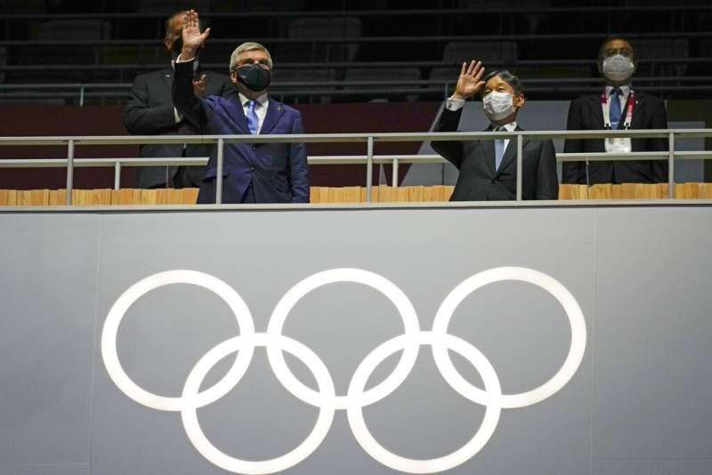 德仁天皇與國際奧會主席巴赫在23日的東京奧運開幕式對場內選手揮手致意。(美聯社)