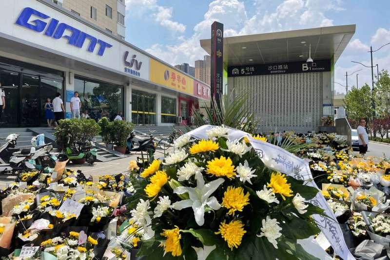 鄭州市民在地鐵五號線入口堆放鮮花,悼念罹難同胞。(美聯社)