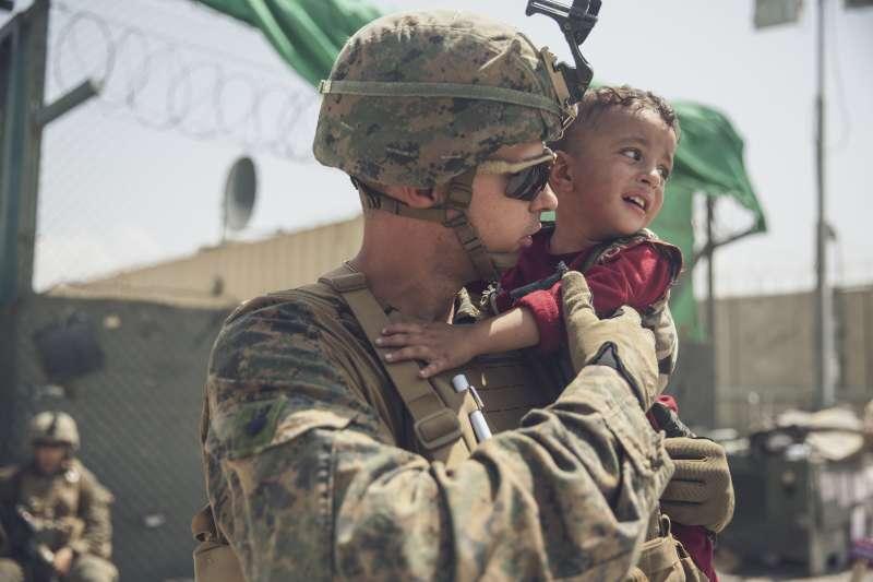 2021年8月22日,喀布爾機場一名美軍正在安撫懷中的阿富汗孩童。(美聯社)