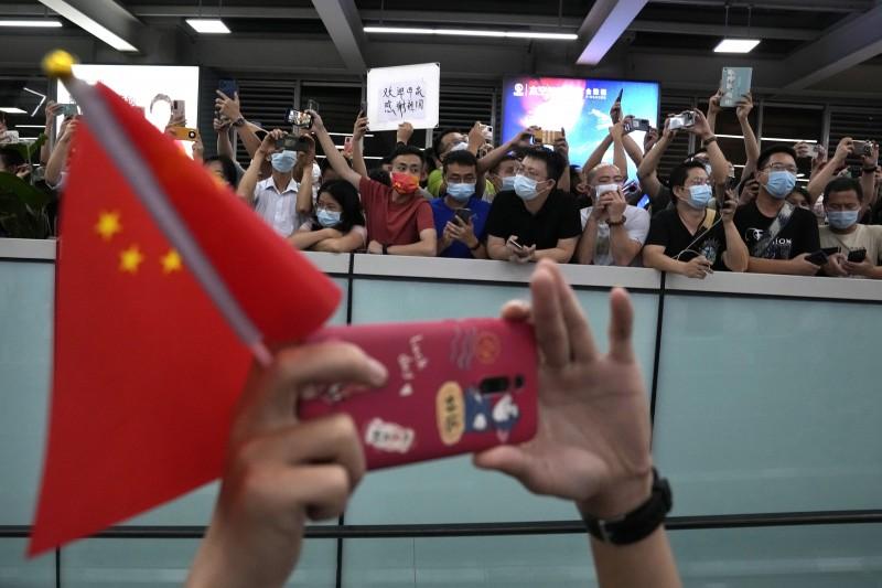 深圳寶安國際機場25日出現大批接機人群,高舉「歡迎孟晚舟回家」的標語。(美聯社)