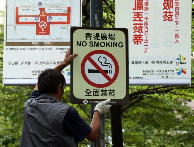 20161101-台北市環保局11月起於信義區香堤廣場禁菸區逕行取締開罰。圖為工作人員將禁菸告示高高掛起-(蘇仲泓攝)