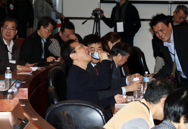 20161216-黨產會今日針對中廣、中影公司案舉行預備聽證會。圖為中廣董事長趙少康會前喝水,為聽證會做準備。(蘇仲泓攝)